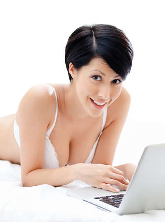 femme en sous vetements: Femme dans les sous-v�tements travaille sur l'ordinateur portable mince, allong� sur le lit, isol� sur fond blanc