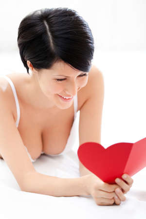 Woman in underwear hands a heart shaped post card while lying on the bed, isolated on white photo