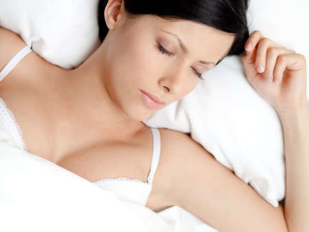 Sleeping woman in the soft bed, white background photo