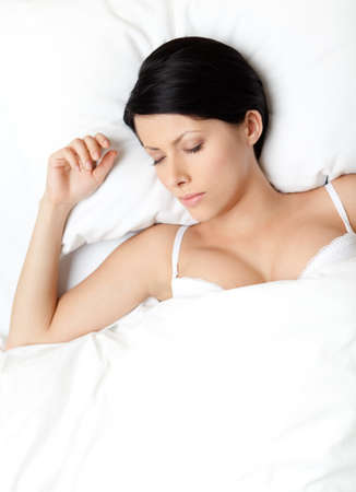 Sleeping woman in the queensize bed, white background photo
