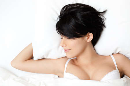 Sleeping sexy woman in the double bed, white background photo