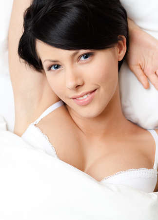 Sleeping sexy woman in the comfortable bed, white background photo
