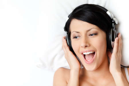 Woman in bra listens to music through the black headphones, white background photo