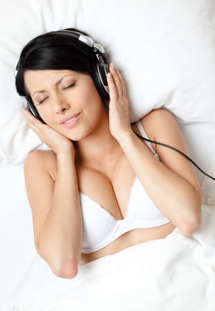 Woman in underwear listens to music through the black earphones, white background photo
