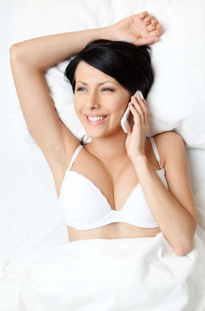 Woman in underwear speaks on telephone while lying in the bed, white background photo