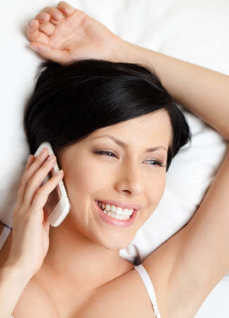 Woman in underwear speaks on cellphone while lying in the bed, white background photo