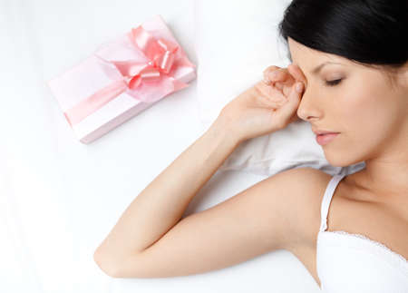 Sleeping woman and present wrapped in pink paper on the bed, white background photo