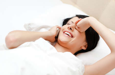 Woman in underwear speaks on cellular while lying in the bed, white background photo