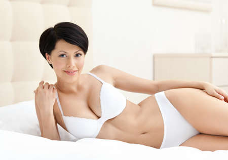 Woman in white perfect bra is lying in the soft bed with white bedclothes photo