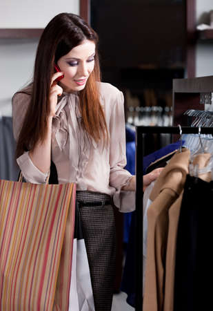 Young woman speaks on the cellphone and choosing clothes in the store photo