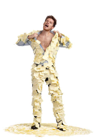 A young man ripping off his shirt, covered with stickers, isolated on white, full-length portrait photo