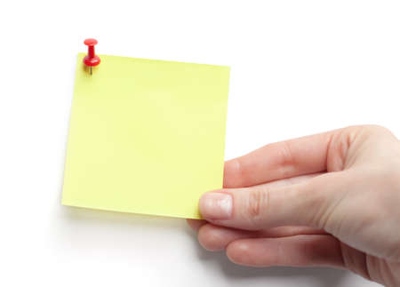 assert: Hand with yellow sticky note on white background