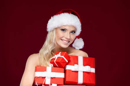 Beautiful lady in Christmas cap holds a set of gifts wrapped with red paper, isolated on purple Stock Photo - 15075636