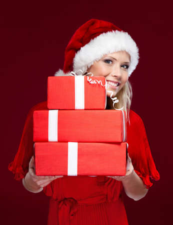 Attractive woman in Christmas cap hands a set of presents, isolated on purple Stock Photo - 15044467