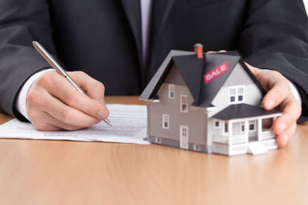 Real estate concept - businessman signs contract behind house architectural model photo
