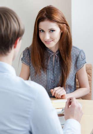conversaciones: Mujer habla con el hombre sentado a la mesa en la cafetería Foto de archivo