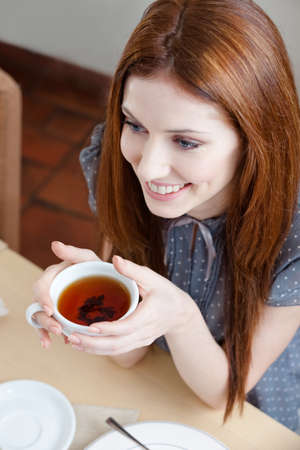 Woman with cup of tea at the coffee house photo