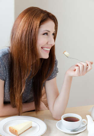 Woman is eating the cake at the restaurant Stock Photo - 15044450
