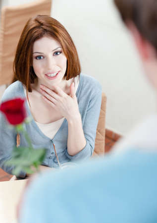Man presents a crimson rose to his girlfriend at the coffee house Stock Photo - 15044470