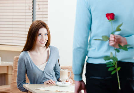 unexpected: Man keeps crimson rose behind his back to present it to his girlfriend Stock Photo