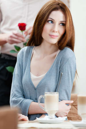 Woman at the cafe and man with red rose behind her photo