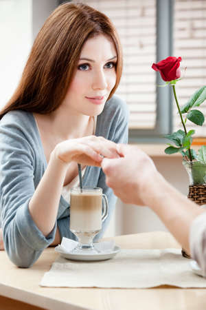 Woman with red rose at the cafe hand in hand with her boyfriend photo