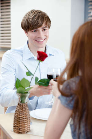 Pair is at the restaurant sitting at the table with vase and scarlet rose in it photo