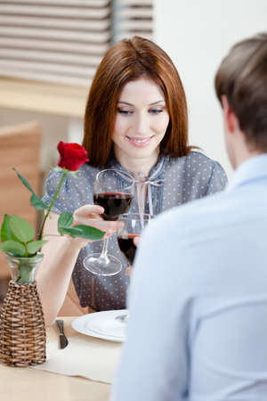 Pair is at the coffee house sitting at the table with vase and scarlet rose in it Stock Photo - 15044381
