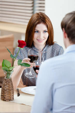 Couple is at the restaurant sitting at the table with vase and crimson rose in it photo