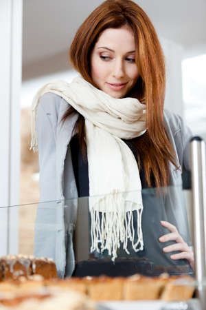 bakery shop: Woman in scarf looking at the bakery window full of different pieces of pies Stock Photo