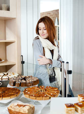 Woman in scarf looking at the bakery showcase full of different pieces of tarts photo