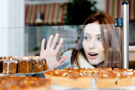 Woman in scarf looking at the bakery window full of different pieces of tarts photo