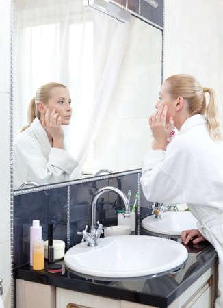 bewonderen: Jong meisje in badjas kijkt naar de spiegel in de badkamer
