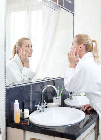 woman mirror: Young girl in bathrobe looks at the mirror in bathroom Stock Photo