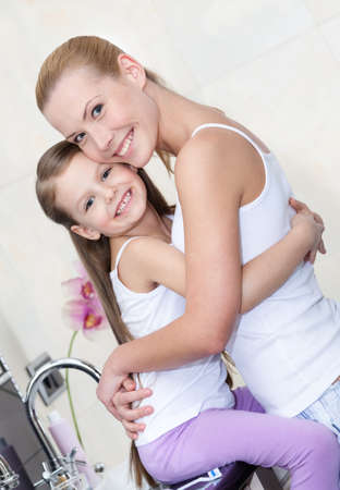 genegenheid: Moeder en dochter omhelzen elkaar in de badkamer. Vertrouwensrelatie