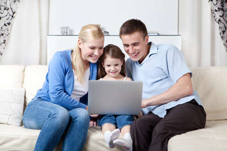 Happy family of three make purchases through the internet sitting on the couch photo
