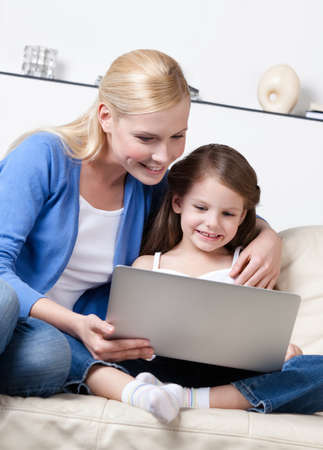 Little child surfs on the internet with her mum sitting on white leather sofa photo