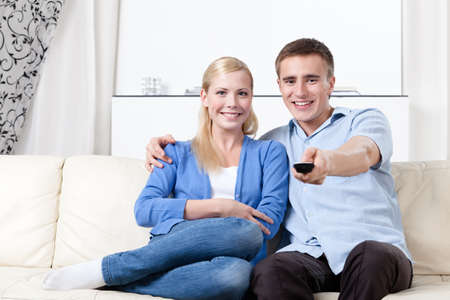 Sitting on the white leather sofa couple is going to watch TV set photo