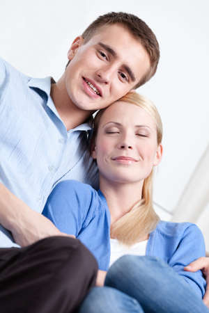 two minds: Man and his girlfriend embrace each other on the white sofa