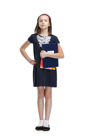 Strict schoolgirl carries her books, isolated, white background photo