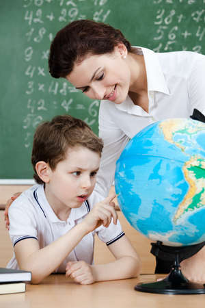 educator: Little schoolboy is looking for something at the terrestrial globe Stock Photo