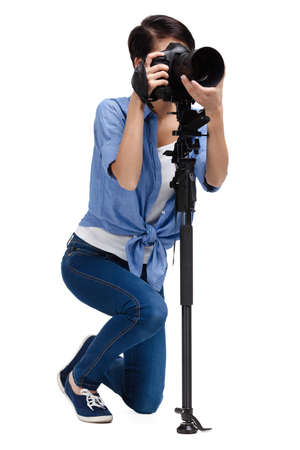 camera operator: Woman takes images holding photographic camera, isolated on white background Stock Photo