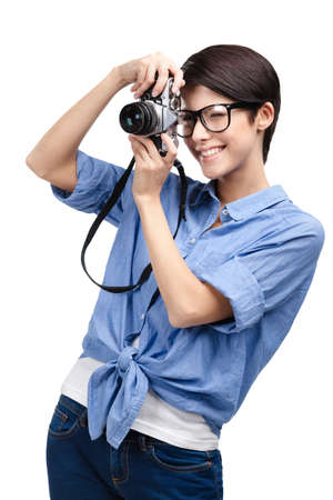 camera operator: Woman in spectacles makes photos with retro photographic camera, isolated on white