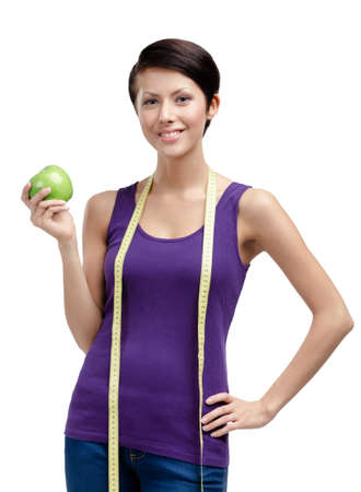ideal: Loosing weight woman with flexible ruler and green ripe apple, isolated on white
