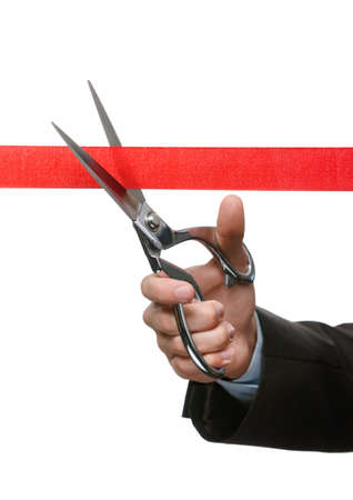 A business man cutting a satin ribbon with scissors, isolated on white photo