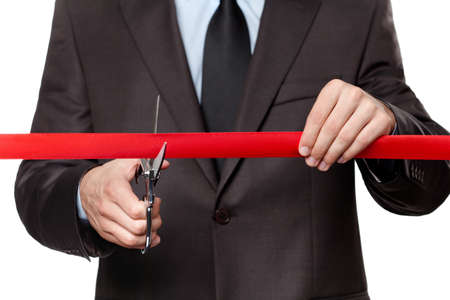 new business: A man cutting a scarlet satin ribbon with scissors, isolated on white Stock Photo