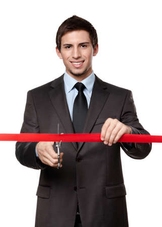 A man cutting a red ribbon with scissors, isolated on white photo