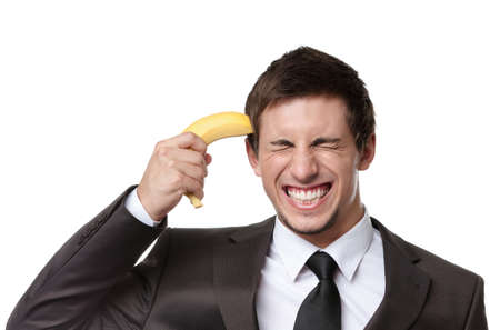disappointment: Business man gesturing gun with banana, isolated on white