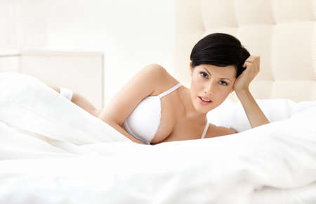 lie down: Woman in white bra is lying in the bedstead with bedclothes Stock Photo