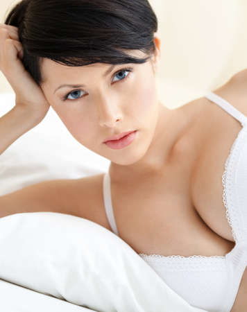 lying on side: Woman in underwear is lying in the double bed with white bedclothes